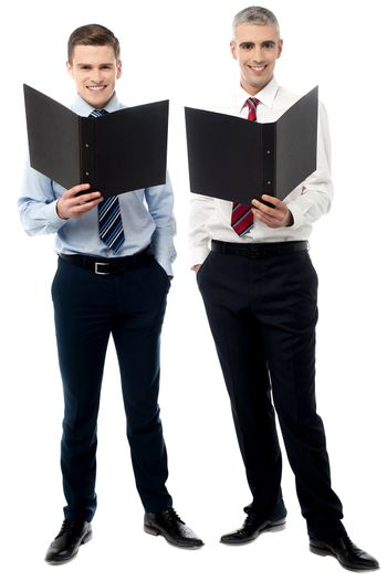 Young male executive posing with file folder