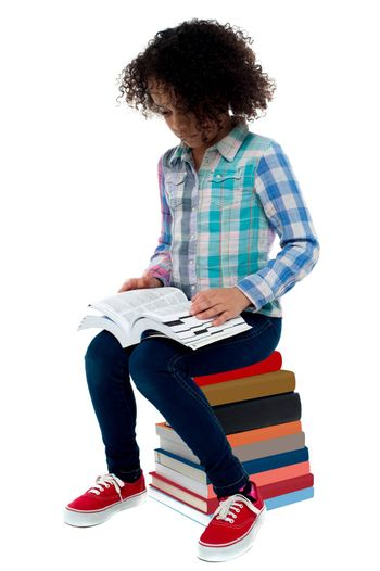 School girl sitting on stack of book and reading