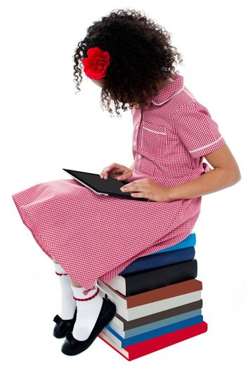 School girl sitting on books with digital tablet