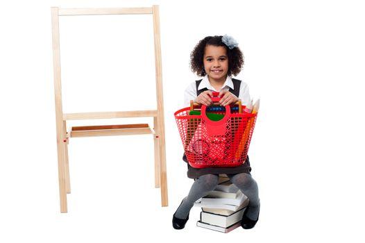 School kid sitting on stack of books near board