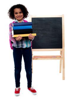 Smiling little girl carrying school books over white