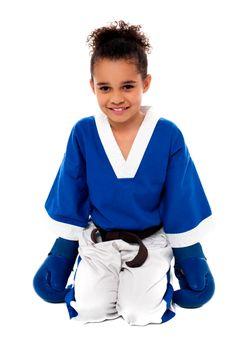Happy karate girl sitting on floor after practice