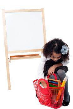 Little girl taking something from her basket bag