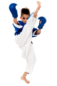 Little karate kid kicking by a leg
