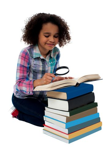 Little girl reading a book using magnifying glass
