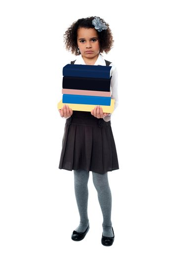 Unhappy girl holding stack of school books
