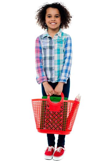 Little girl standing with basket bag over white