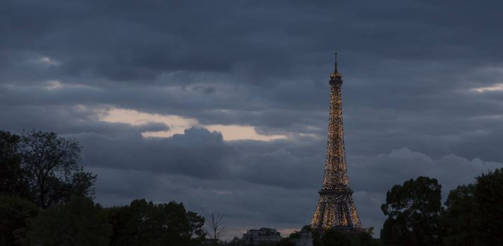 Eiffel Tower in Paris, France Sparkeling at Night with clouds behind it.