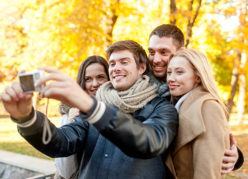 relationship, season, friendship, technology and people concept - group of smiling men and women making self portrait with digital camera in autumn park