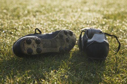 football boots on a empty football pitch,frosty winter morning s