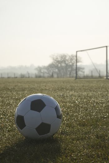 black and white football on a empty football pitch,frosty winter