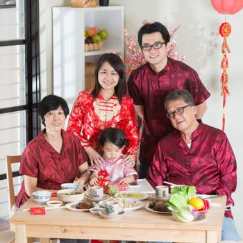 Spring seasons Chinese New Year, reunion dinner. Happy Asian Chinese multi generation family with red cheongsam taking group photo while dining at home.
