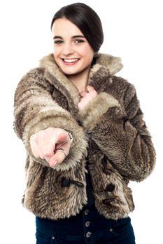 Smiling girl in fur coat, pointing her finger forward.