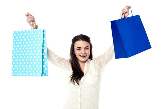 Excited girl holding up her shopping bags