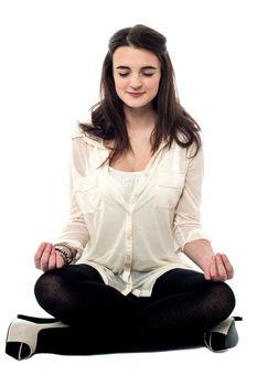 Teen girl practicing yoga in lotus position