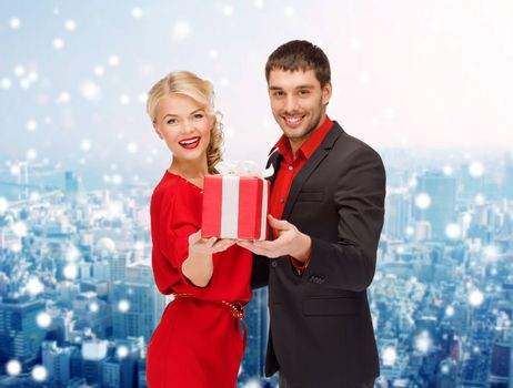 christmas, holidays, valentine's day, celebration and people concept - smiling man and woman with present over snowy city background