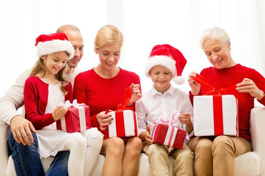 family, holidays, generation, christmas and people concept - smiling family opening gift boxes at home
