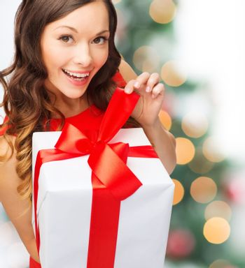 christmas, xmas, celebration concept - smiling woman in red dress with gift box