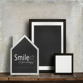 Chalkboard with quote and frames on old table