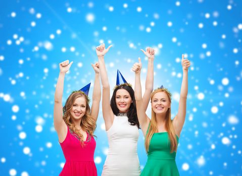 holidays, christmas, people, gesture and celebration concept - smiling women in party caps showing thumbs up over blue snowy background