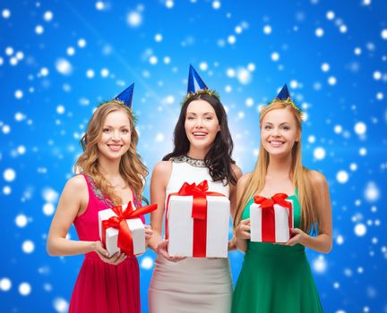 presents, holidays, people and celebration concept - smiling women in party caps with gift boxes over blue snowing background