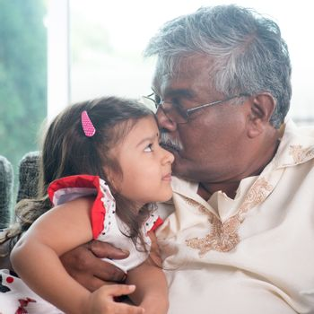 Portrait of Indian family at home. Grandparent kissing grandchild. Grandfather and granddaughter. Asian people living lifestyle.