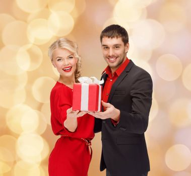 christmas, holidays, valentine's day, celebration and people concept - smiling man and woman with present over beige lights background
