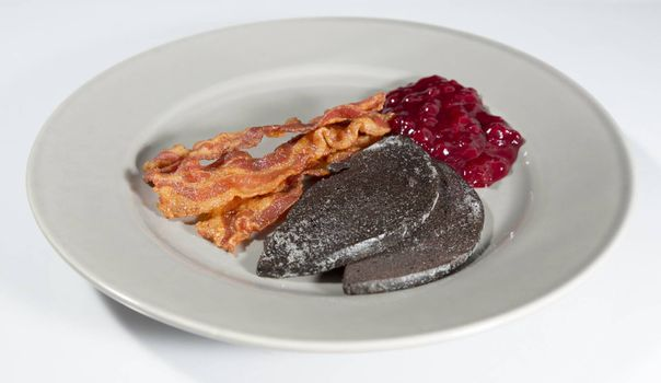 Swedish Blood Pudding with Bacon and Lingonberry Jam on plate with white background.