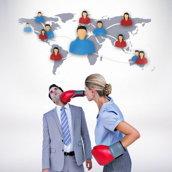 Composite image of businesswoman punching colleague with boxing gloves