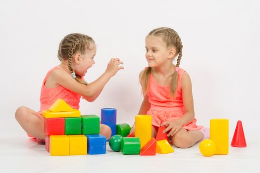 Girl frighten another girl playing with blocks