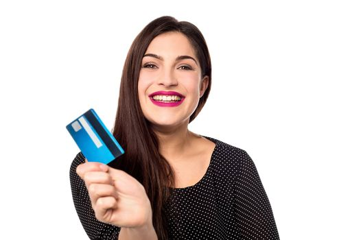 Cheerful young woman showing her credit card