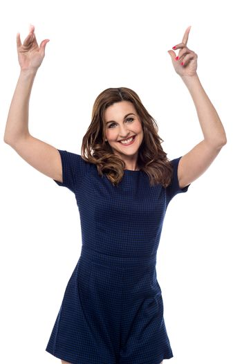 Happy woman pointing her finger upwards