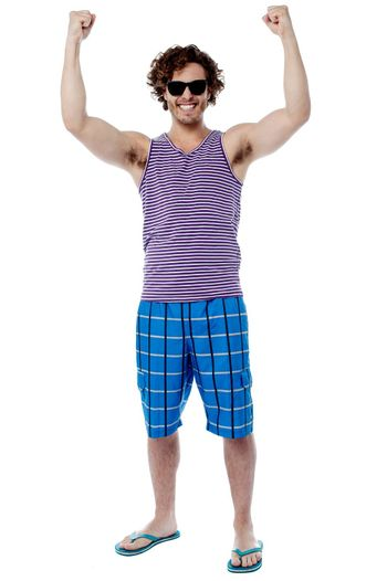 Full length of excited male raising his arm