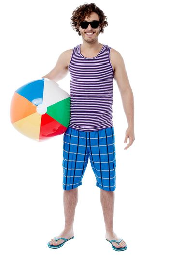 Handsome young guy posing with beach ball