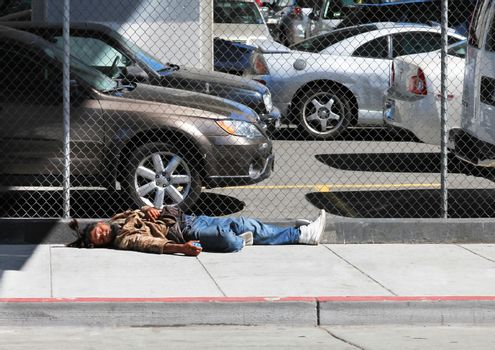 Los Angeles, CA, USA - September 23, 2011: Homeless man sleeps on the street near the fence in the center of Los Angeles