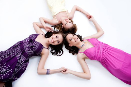 Three young smiling women liying on  a studio floor