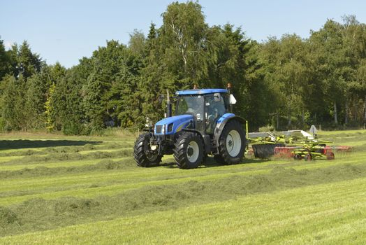 Agriculture, the kidding of shaken grass with blue tractor with kidder