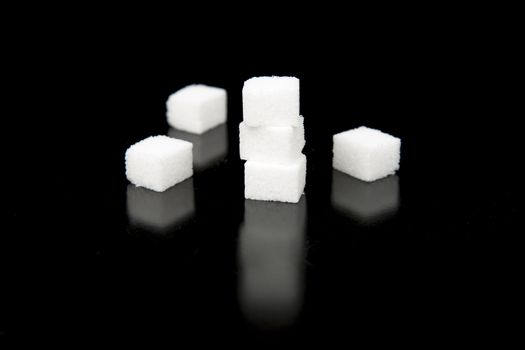 Sugar Cubes with Black Background lying on top and spread out.