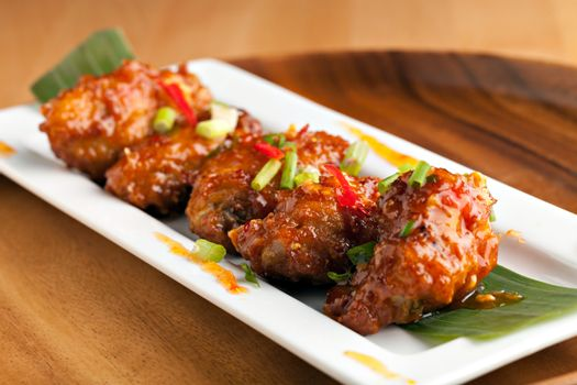 Thai style spicy chicken wings appetizer on a contemporary white plate.  Shallow depth of field.