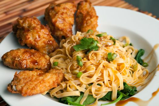 Thai style fried chicken wings on a round white plate with egg noodles and spinach. Shallow depth of field.