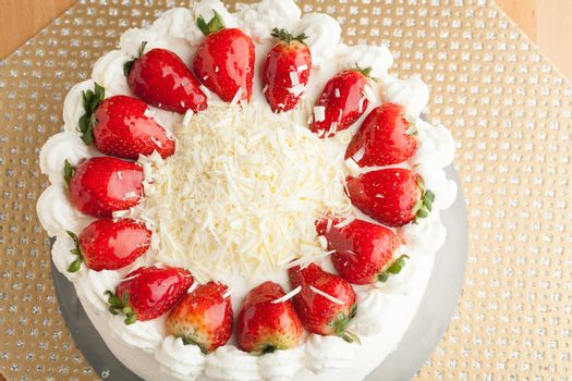 Top view of an entire strawberry shortcake with white chocolate shavings.  Shallow depth of field.
