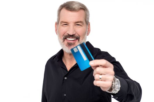 Senior man showing his credit card to camera