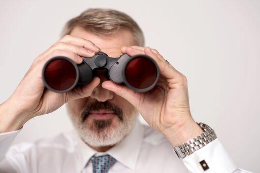 Image of a elder businessman observing through binoculars