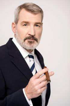 Portrait of confident businessman smoking a cuban cigar
