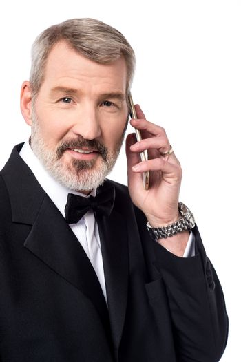 Mature man talking over the phone on white background