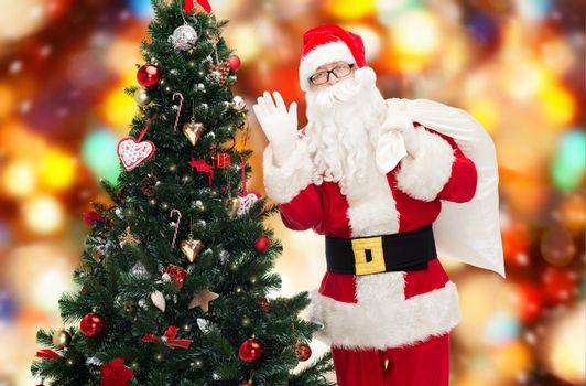 christmas, holidays and people concept - man in costume of santa claus with bag and christmas tree waving hand over red lights background
