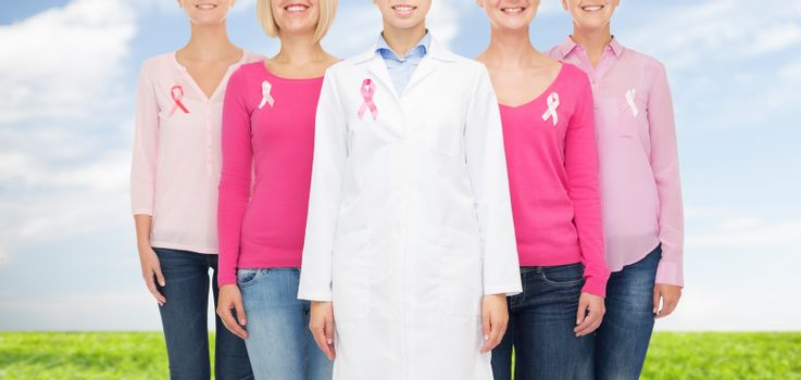 healthcare, people and medicine concept - close up of smiling women in blank shirts with pink breast cancer awareness ribbons over blue sky and grass background