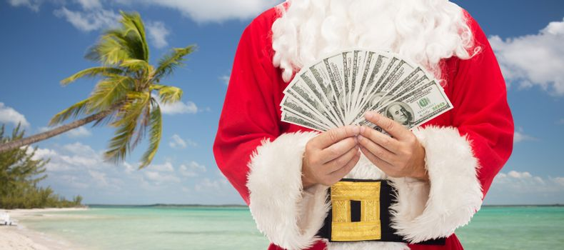christmas holidays, winning, currency, travel and people concept - close up of santa claus with dollar money over tropical beach background