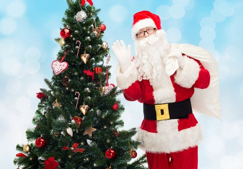 christmas, holidays and people concept - man in costume of santa claus with bag and christmas tree waving hand over blue lights background