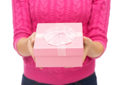 christmas, holidays and people concept - close up of woman in pink sweater holding gift box
